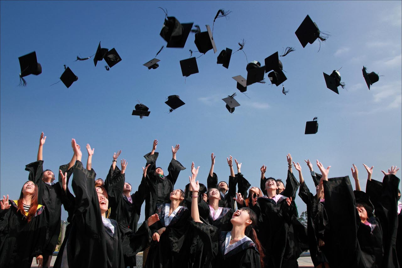 University graduates celebrating and throwing their caps in the air