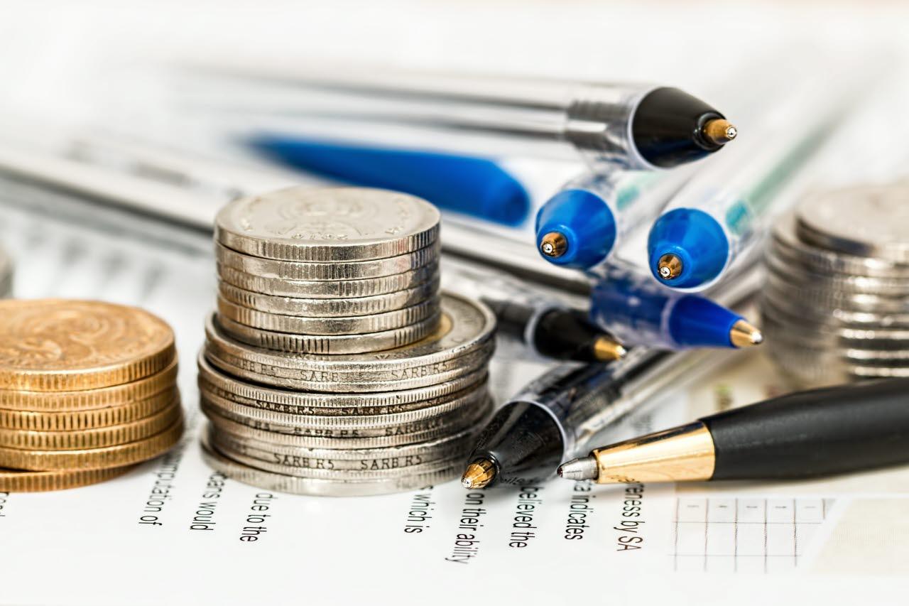 Coins beside ballpens