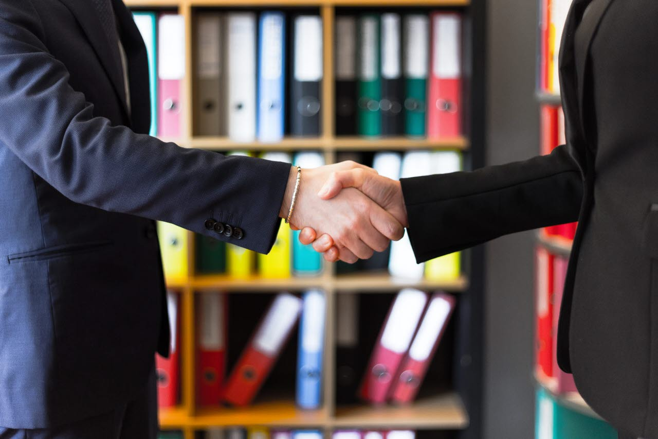 Two businesspeople shaking hands in an office