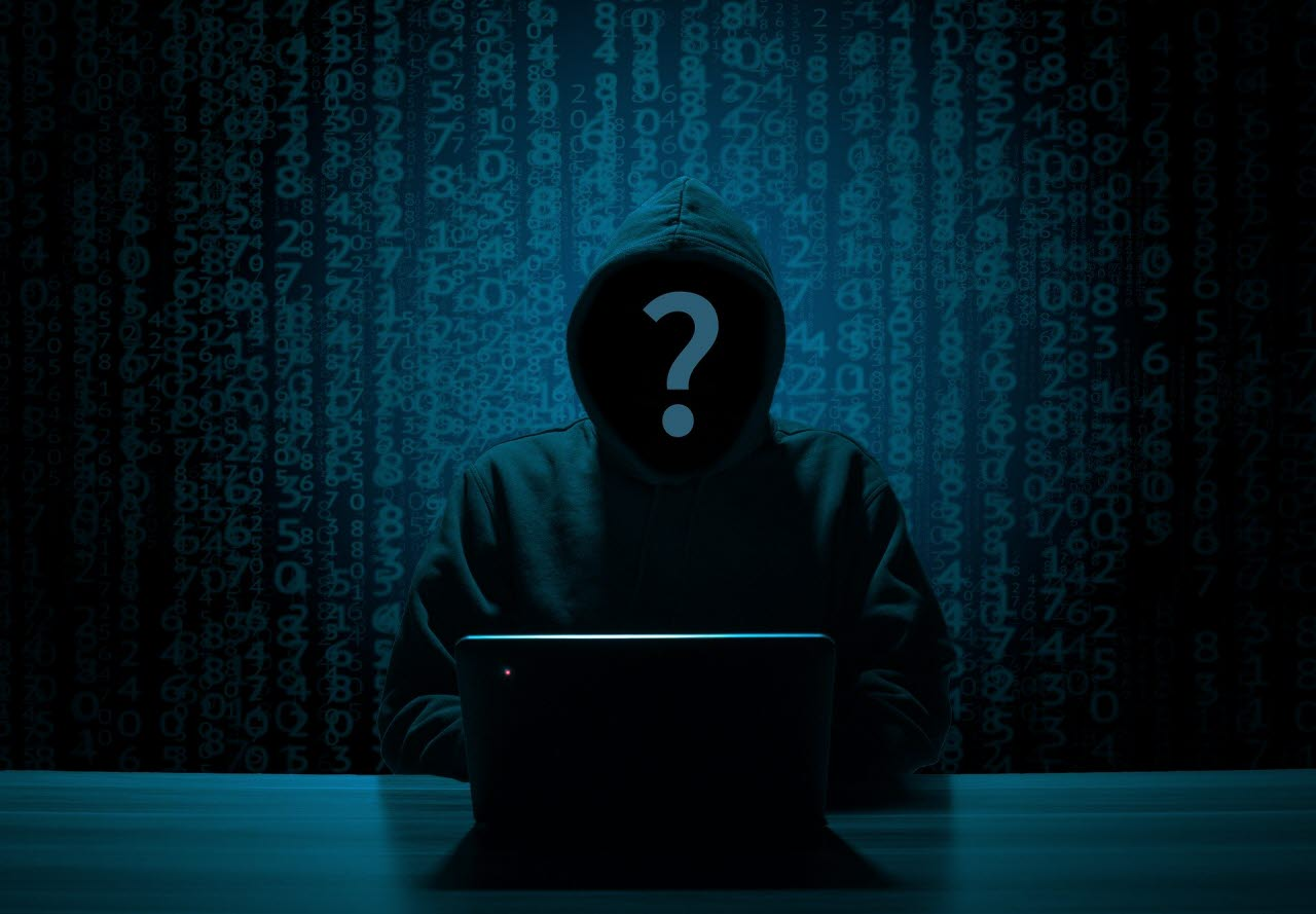 Image of silhouetted person with hood in front of computer committing cybercrime